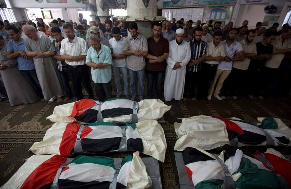 Palestinian mourners pray over five bodies, all from the Halaq family, during their funeral in the Jabalia refugee camp, in the Gaza Strip, on July 21, 2014. World efforts to end two weeks of deadly violence in and around Gaza, that has left over 500 Palestinians deads, stepped up a gear as US Secretary of State and the UN chief both headed to Cairo. AFP PHOTO / MAHMUD HAMS