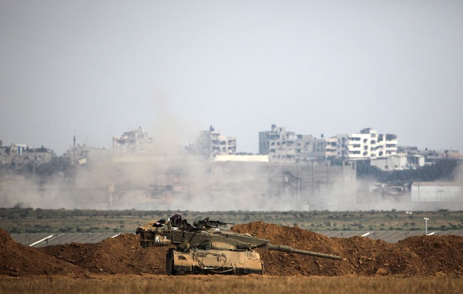 A picture taken from the Israeli side shows an Israeli army Merkava tank positionned along the border in front of buildings in the Gaza Strip on July 28, 2014. The UN Security Council joined US President Barack Obama in calling for an immediate ceasefire in Gaza, after Israel and Hamas ignored calls for a truce despite mounting civilian casualties.  AFP PHOTO/DAVID BUIMOVITCH